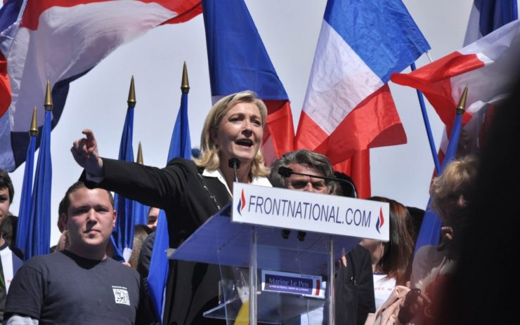 Marine Le Pen hinter einem Rednerpult. Hinter ihr sind französische Flaggen.
