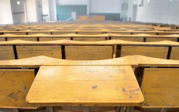 Ein Hörsaal mit mehreren leeren Stuhlreihen, ein Tisch ist aufgeklappt.