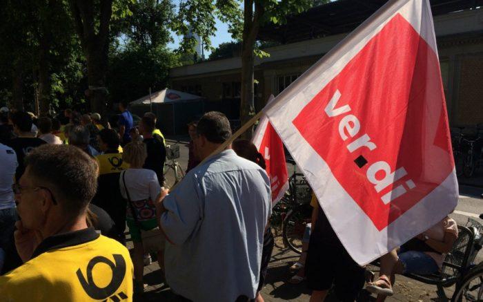 Zwei Streikende, einer mit einer ver.di Fahne, der andere mit einer Jacke der deutschen Post AG.