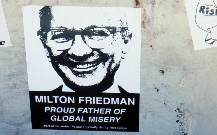 """Ein Aufkleber auf dem Milton Friedman abgebildet ist und der Spruch: """"""""proud father of global misery"""""""