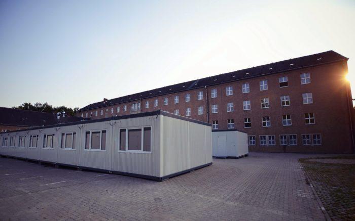 Eine Containerunterkunft im Gegenlicht vor einem Backsteinbau.