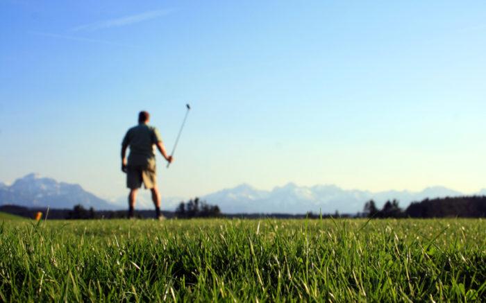 Ein Golfspieler, im Vordergrund ist der Rasen zu sehen, im Hintergrund ein Gebirge.