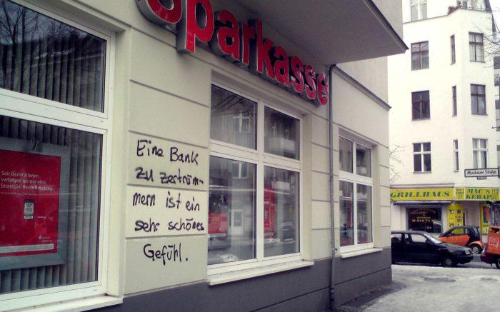 """Eine Sparkassenfiliale, auf deren Fassade jemand den Spruch """"Eine Bank zu zertrümmern ist ein sehr schönes Gefühl"""" gesprüht hat."""