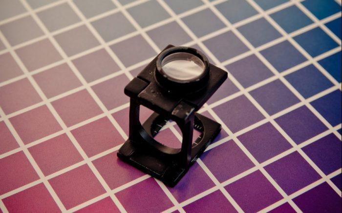 Eine Lupe auf einem Farbspektrum.