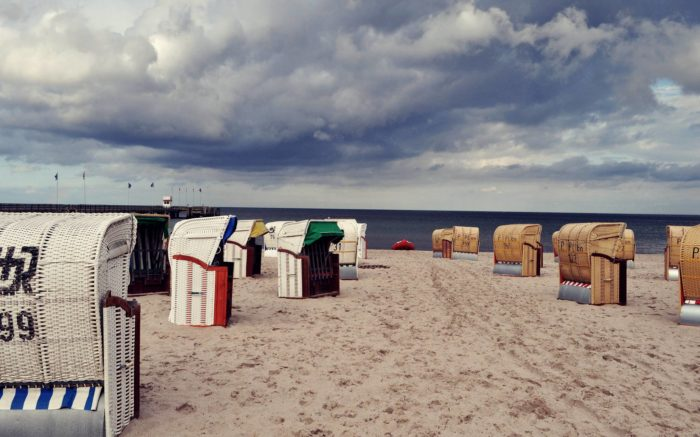 Strandkörbe vor bewölktem Himmel an der Ostsee.