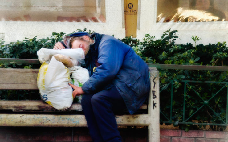 Obdachloser Mann schläft auf einer Bank in einer griechischen Stadt.