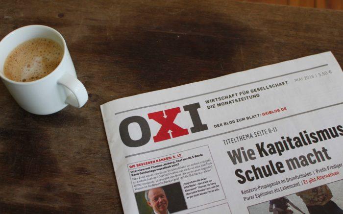 Ein Titelblatt von OXI und eine Kaffeetasse