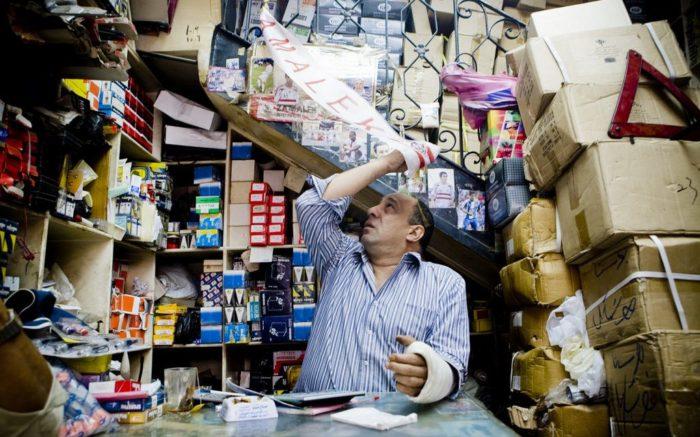 Ein Markthändler in einem engen Verkaufsstand