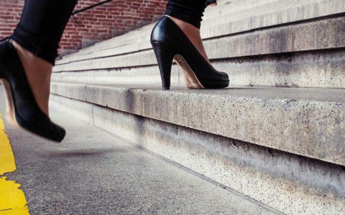 Zwei Füße in High Heels gehen eine Treppe hinauf