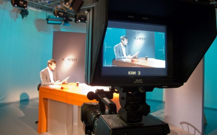 Ein Mann sitzt an einem Tisch und verliest die Nachrichten. Vor ihm eine Kamera. Das ganze ist im Studio von Kontext TV.