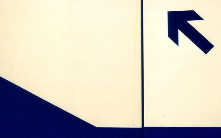An einem Treppengeländer zeigt ein Pfeil nach oben.