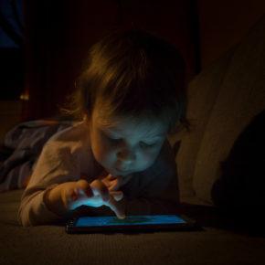 Ein Kleinkind tippt im Dunkeln auf einem erleuchtetetn Tablet.