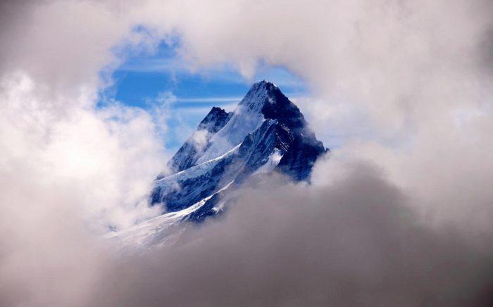 Ein Schweizer Berggipfel inmitten von Wolken.