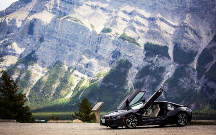 Ein schwarzer glänzender BMW mit aufgeklappten Türen vor Bergkulisse.