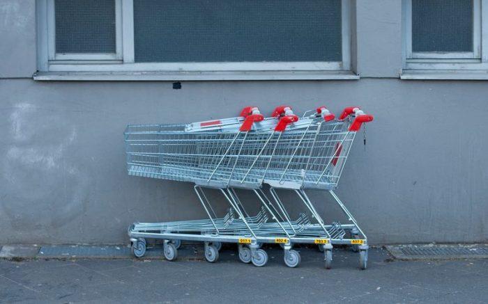 Zusammengeschobene Einkaufswagen vor einer Wand.