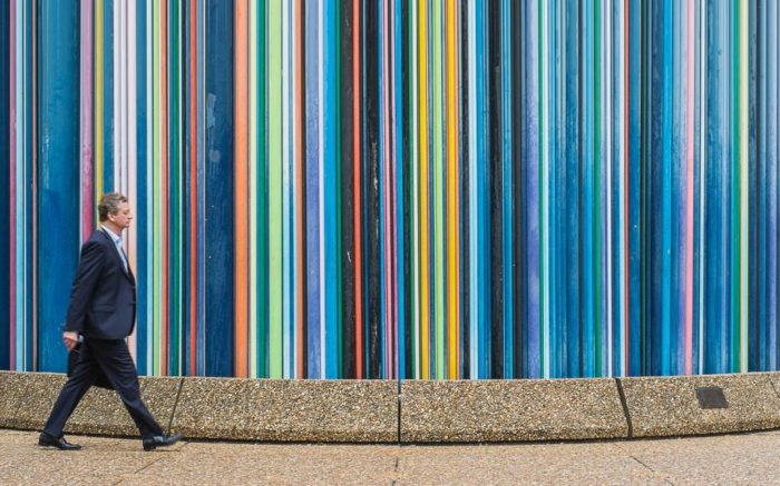 Mann mit Anzug läuft vor farbig gestreifter Wand