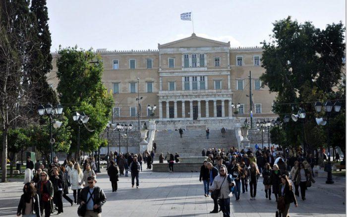 Menschen in Athen laufen auf Platz vor Parlament