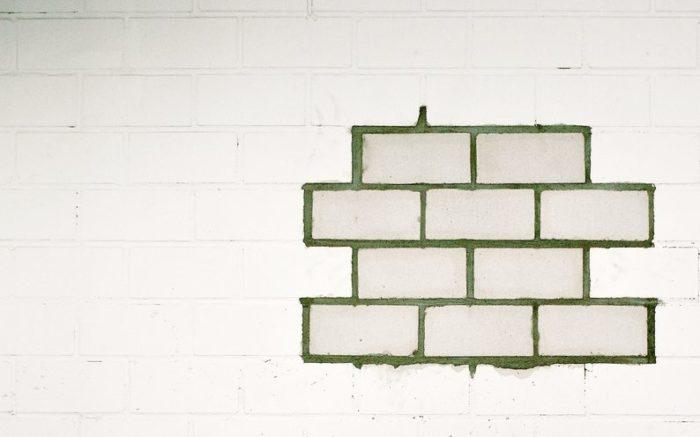 Eine Wand in der einige Steine ausgetauscht wurden.