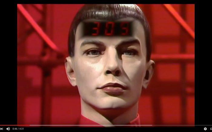 En Musiker der Band Kraftwerk mit einer Zahlenanzeige auf der Stirn.