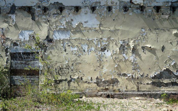 Marode Mauer, von der großflächig Farbe abbröckelt