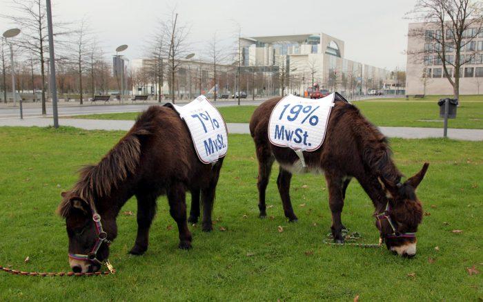 Zwei Esel mit je einer brschrifteten Satteldecke, auf der die Mehrwertsteuersätze 7 und 19 Prozent aufgedruckt sind, grasen auf einer Rasenfläche im Berliner Regierungsviertel. Im Hintergrund ist das Bundeskanzleramt zu sehen.