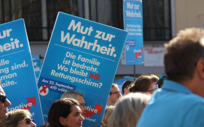 Menschen mit AfD Schildern, nah.