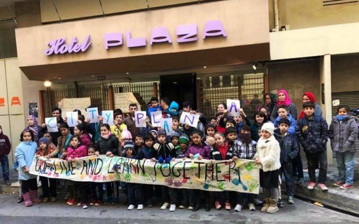 Eine Gruppe Kinder mit Plakat vor dem Eingang des City Plaza Hotels.