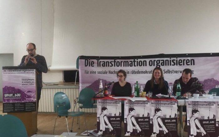 """Vertreter von unter_bau sitzen vor einem Transparent: """"Die Transformation organisieren"""""""