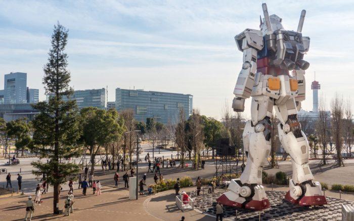 Ein großer Roboter betrachtet einen Gebäudekomplex und Menschen.