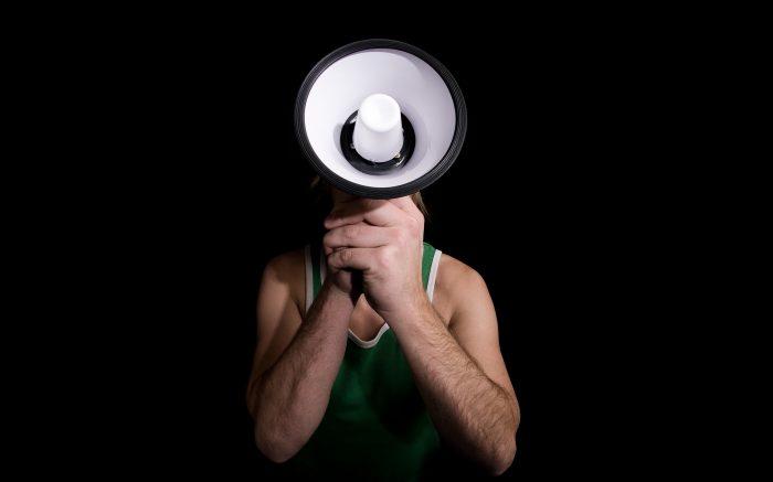 Ein Mann hält ein Megafon vor sein Gesicht. Kommunikation.