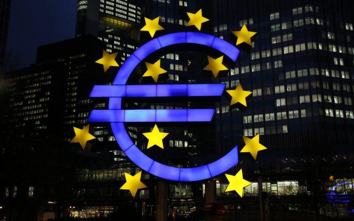 blau leuchtende Euro-Skulptur mit gelben Sternen nachts, mit Häusern im Hintergrund