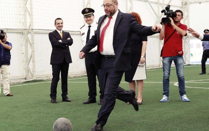 Martin Schulz tritt, umringt von Journalisten, einen Fußball.