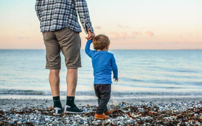 Ein Mann hat ein kleines Kind an der Hand. Sie blicken auf das Meer hinaus.