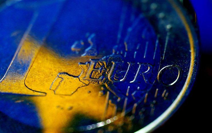 In einer Euromünze spiegelt sich die Fahne der EU. Nahansicht.