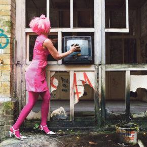 Frau in Pink hat Stein in Hand und versucht ein Fernsehgerät damit zu zerschlagen