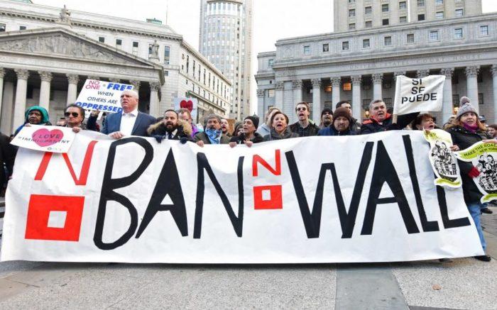Demonstranten mit einem Transparent. Aufschrift: No Ban, No Walls.