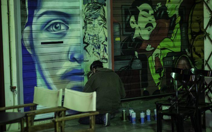 Graffittikünstler knieend vor seinem Bild