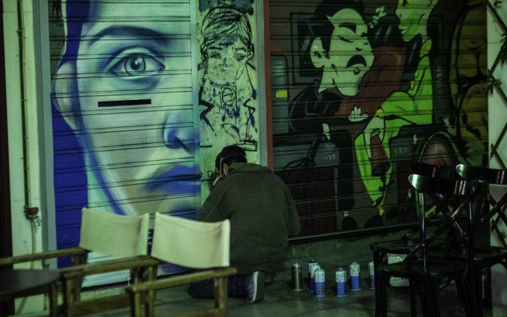 Graffittikünstler in Exarchia kniet vor seinem Bild