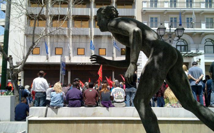Skulptur eines Läufers im Vordergrund, im Hintergrund sitzende Menschen einer Straßenversammlung