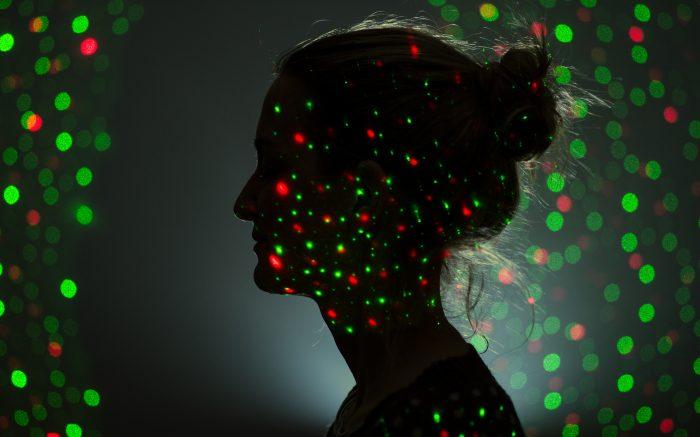 Das Schattenbild einer Frau. Davor viele Punkte, die den Eingriff durch KI symbolisieren sollen.