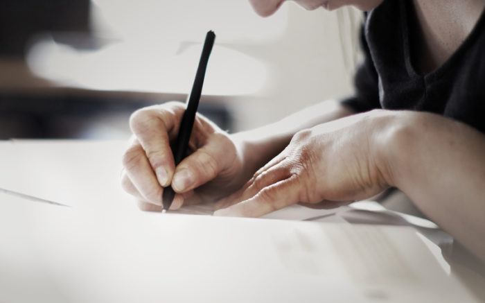 Frau schreibt in Heft, close