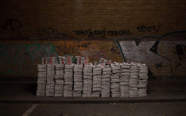 Mehrere Stapel Zeitungen nebeneinander.