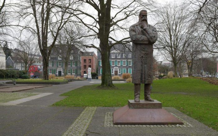 Die Statue von Friedrich Engels in Wuppertal. Stehend mit Hand am Bart. Anderer Arm ist verschränkt.