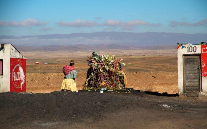 Eine Sammlung an Gegenständen zwischen zwei Hütten. Daneben eine Frau in klassischem indigenen Kleidungsstil.