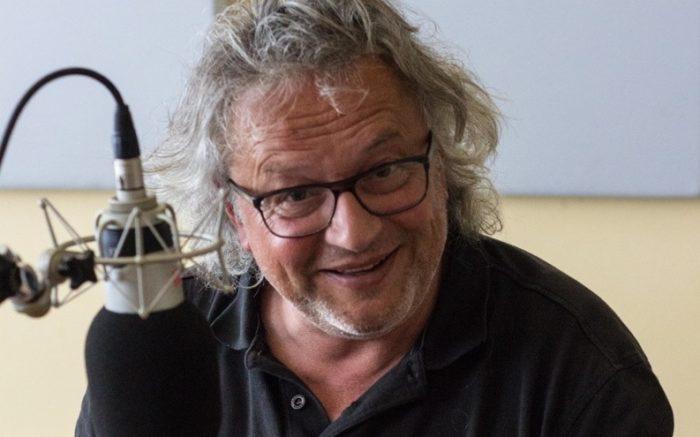 Klaus Doerre am Mikro, in Kamera lachend