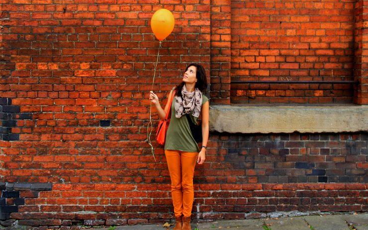 Frau mit Luftballon vor Mauer,