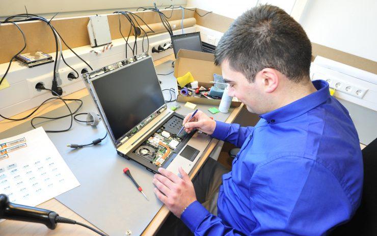 Mann mit Handicap am Arbeitsplatz, repariert Laptop