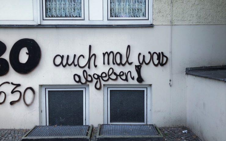"""Schwarzes Graffiti auf der Wand: """"auch mal was abgeben!"""" in Schreibschrift. darunter Kellerfenster, darüber Fenster mit Spotzen-Gardinen."""