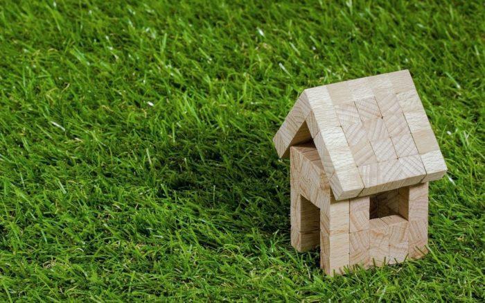 Gute Investition: Ein Haus aus Bauklötzen steht auf grünem Rasen.
