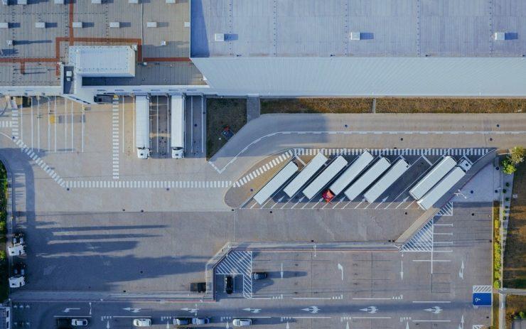 Ein Logistikzentrum von oben mit LKWs, die auf einem Parkplatz stehen. Lager von Amazon sehen ähnlich aus.